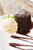 Chocolate cake with rum raisin ice cream and whipping cream on w Stock Photos