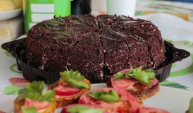 Chocolate cake and sandwiches with tomatoes royalty free stock photography