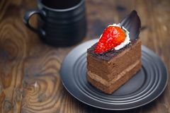 Chocolate cake in saucer next to mug of coffee on distressed woo stock images