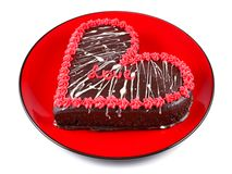 Chocolate cake in the shape of a heart with the word love on a red plate Royalty Free Stock Image