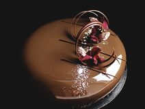 Chocolate cake with shiny mirror glaze and flower petals. Chocolate cake with shiny mirror glaze, carnation petals and almonds royalty free stock photo