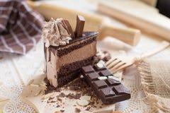 Chocolate cake slice with chocolate cream and chocolate bar. cake background concept.  stock photo