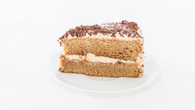 Chocolate cake slice with curl on white dish. White background Royalty Free Stock Photography