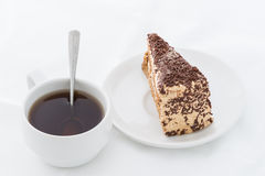 Chocolate cake slice with curl on white dish with hot drink. White background Royalty Free Stock Image