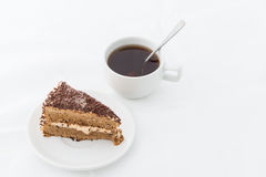 Chocolate cake slice with curl on white dish with hot drink. White background Royalty Free Stock Photo