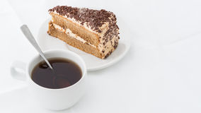 Chocolate cake slice with curl on white dish with hot drink. White background Royalty Free Stock Images