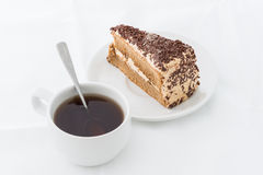 Chocolate cake slice with curl on white dish with hot drink. White background Stock Photos