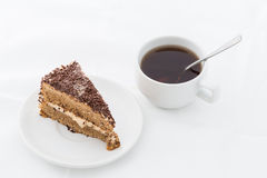 Chocolate cake slice with curl on white dish with hot drink Royalty Free Stock Photos