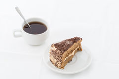 Chocolate cake slice with curl on white dish with hot drink. White background Stock Image