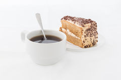 Chocolate cake slice with curl on white dish with hot drink. White background Royalty Free Stock Photos
