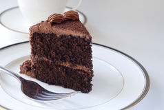 Chocolate cake. A slice of chocolate cake with a fork and a cup of coffee in the background stock image