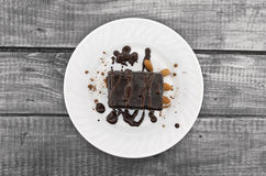 Chocolate cake slice with nut on plate on wooden table, top view Royalty Free Stock Photos