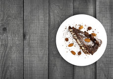 Chocolate cake slice with nut on plate on wooden table, top view Stock Photos