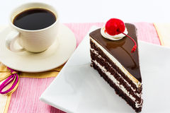 Chocolate cake slice with red cherry fruit and coffee. Stock Image
