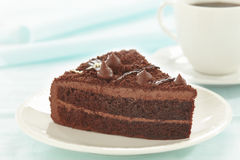 Chocolate cake slice on white plate. And coffee cup royalty free stock photos