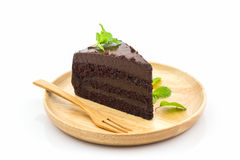 Chocolate cake slice. Chocolate cake slice in wooden plate on white background royalty free stock image