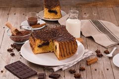 Chocolate cake. Chocolate cake with spices on wooden table royalty free stock photo