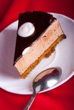Chocolate cake with spoon on red silk background Stock Photography