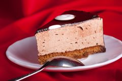 Chocolate cake with spoon on red silk background Royalty Free Stock Photos