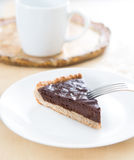 Chocolate cake with stainless steel fork, white ceramic dish and white cup in the background Stock Photo