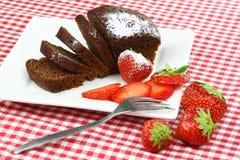 Chocolate cake and strawberries. One cut chocolate cake on a white plate with some strawberries Royalty Free Stock Photo