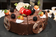 Chocolate cake with strawberries on brown plate Stock Images