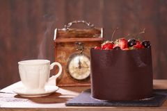 Chocolate cake with strawberries and cherries lying on a wooden table. stock image
