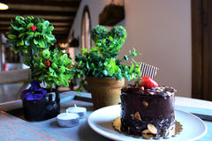Chocolate cake with strawberries on top, sprinkled with nuts on. A white plate. candles and green plants in the background Royalty Free Stock Image