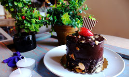 Chocolate cake with strawberries on top, sprinkled with nuts on. A white plate. candles and green plants in the background stock photos