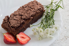 Chocolate Cake with Strawberries and White Flowers. Homemade Chocolate Cake with Strawberries and White Flowers on a White Plate Royalty Free Stock Photography