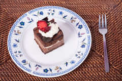 Chocolate cake with strawberry,fork and hand. Chocolate Cake in plate with strawberry Stock Photography