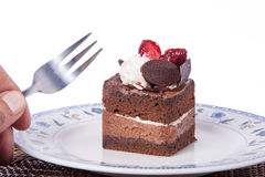 Chocolate cake with strawberry,fork and hand. Chocolate Cake in plate with strawberry Stock Image