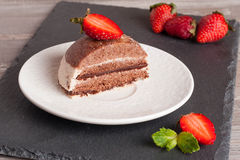 Chocolate cake with strawberry on wooden table, horizontal. Chocolate cake with strawberry on wooden table close-up Stock Photo
