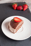 Chocolate cake with strawberry on wooden table, vertical. Chocolate cake with strawberry on wooden table top up Royalty Free Stock Photo