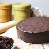Chocolate cake. A chocolate cake on the table with a kneader, a chocolate bowl and other baking equipment. Square format Stock Image