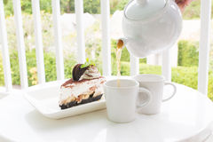 Chocolate cake with tea set in garden Royalty Free Stock Image