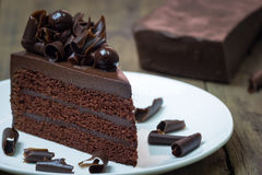 The chocolate cake topping with chocolate curl on wood background. Chocolate cake topping with chocolate curl on wood background Royalty Free Stock Photography
