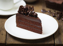 The chocolate cake topping with chocolate curl on wood background. Chocolate cake topping with chocolate curl on wood background Stock Image