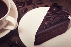 Chocolate cake topping with chocolate curl on wood background, v. Intage toning Stock Photography