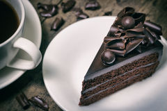 Chocolate cake topping with chocolate curl on wood background, v. Intage toning Stock Photos