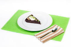 Chocolate cake with topping on green napkin, isolated on white Royalty Free Stock Image