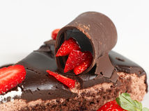 Chocolate cake and truffle. Macro picture of a chocolate cake with strawberry on white background Royalty Free Stock Photos