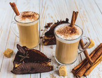Chocolate cake, two cups of cappuccino and spices Royalty Free Stock Image
