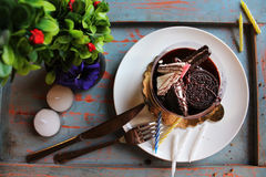 Chocolate cake with waffle and biscuits on top, sprinkled with n. Uts on a white plate. candles and green plants in the background in bakery royalty free stock image