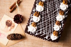 Chocolate cake with whipped cream and walnut. On a festive table with Christmas decorations, fir cones, cinnamon sticks and a greeting card, top view Royalty Free Stock Images