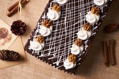 Chocolate cake with whipped cream and walnut. On a festive table with Christmas decorations, fir cones, cinnamon sticks and a greeting card, top view Stock Photography