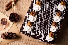 Chocolate cake with whipped cream and walnut. On a festive table with Christmas decorations, fir cones, cinnamon sticks and a greeting card, top view Stock Photo