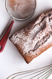 Chocolate cake, whisk,  strainer on white plate. Top view Stock Photo