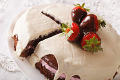 Chocolate cake with white icing and strawberries close-up. Horiz Royalty Free Stock Photography