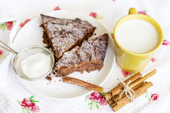 Chocolate cake in a white plate with cinnamon sticks Stock Image